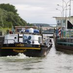 Eine beladene Péniche fährt in eine Schleuse des Canal du Nord ein