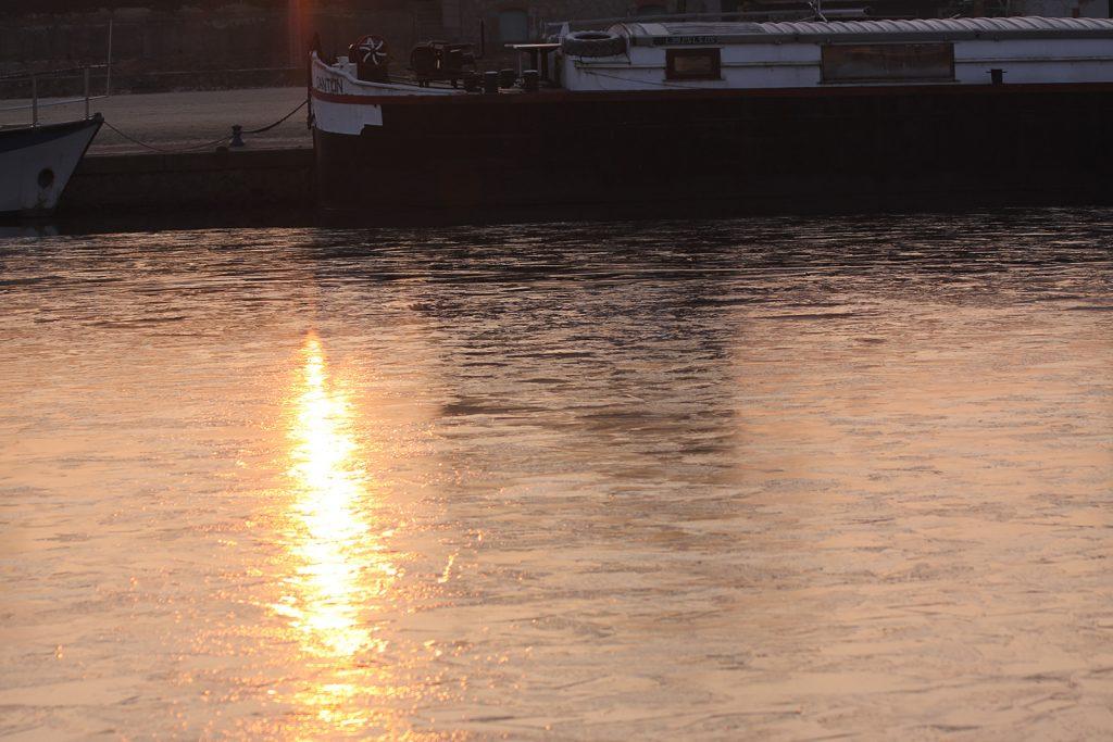 Die aufgehende Sonne spiegelt sich im Eis des Hafenbeckens